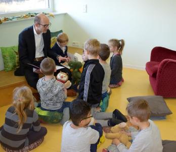 """Robert Langhans, kaufmännischer Leiter von Piening Personal, liest acht Kindern der Fuchs Gruppe """"Geschichten der freundlichen Drachenfamilie"""" vor / Quelle: Piening Personal"""
