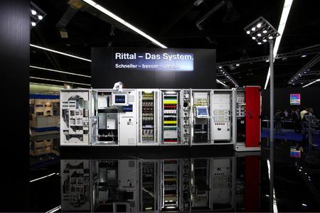 """Rittal - Das System: Schneller - besser - überall"""" - unter diesem Motto präsentiert Rittal auf der Light + Building eine eindrucksvoll inszenierte Systemarchitektur: von der Gehäusetechnik, Stromverteilung über die System-Klimatisierung bis hin zur IT-Infrastruktur"""