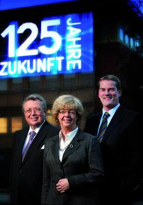"""With a consistently perfect and standard-conform quality, our objective is to reliably fulfil customer demands, strengthen our technological leadership in the market and secure the future of our family-owned company,"" is emphasized by the 4th generation partners Dr Reinhold Festge, Susanne Festge and Walter Haver (from the left) / In the background, the IMAGIC WEAVE® façade of the Wire Weaving Division displays the anniversary logo"