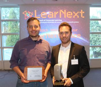 Christian Steiner (senselab.io) und Oswin Breidenbach (TÜV SÜD Akademie GmbH) (v.l.n.r.) nehmen den Immersive Learning Award entgegen