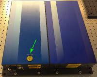 Größenvergleich: Der kleine Strich, auf den der Pfeil zeigt, ist ein Chip, der mit bis zu zehn Femtosekundenlasern ausgestattet werden kann. Der blaue Kasten dagegen ist ein einzelner konventioneller Laser. Bild: CFEL / Neetesh Singh
