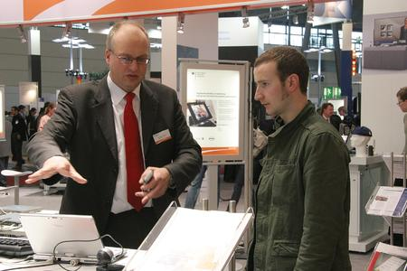 Dr. Jürgen Tacken (left) explains the simple configuration of two context-based mobile services to a visitor.