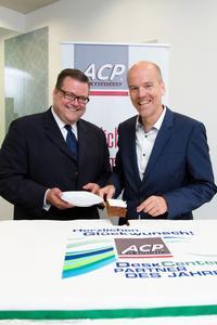 DeskCenter überraschte die ACP-Mitarbeiterinnen und Mitarbeiter am Standort Wien mit einer Riesentorte (v.l.): Christoph Harvey, Vorstand der DeskCenter Solutions AG, und Rainer Kalkbrener, CEO der ACP Gruppe, beim Anschneiden der süßen Aufmerksamkeit.