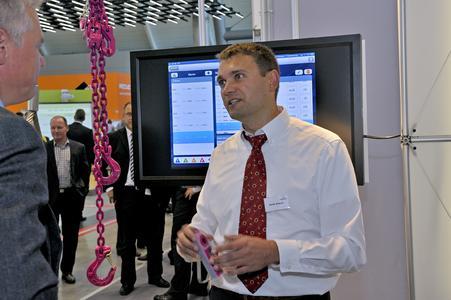 IT-Leiter Stefan Aubele stellt auf der AMB die neueste Entwicklung der Carl Stahl GmbH vor: Kunden lassen sich wissbegierig erklären, wie ein RFID-Lesegerät die Daten etwa einer Zurrkette in das Smart Guard-Programm einspielt und per Checkliste überprüft (FOTO: CARL STAHL)