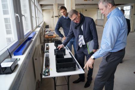 Wirtschaftsminister Buchholz begutachtet eine Lösung zur Behälteridentifikation