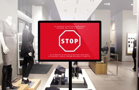 Ein Monitor im Eingangsbereich zeigt anhand eines Ampelsystems dem sich nähernden Kunden, ob er den Laden in diesem Moment betreten darf – oder ob die maximale Kundendichte in der Filiale bereits erreicht ist / Bild:  © ABUS