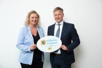 """Kerstin Schreyer (links), Staatsministerin für Familie, Arbeit und Soziales, übergibt das Emblem """"Inklusion in Bayern – Wir arbeiten miteinander!"""" an Dieter Hahn, Managing Director der auticon GmbH"""