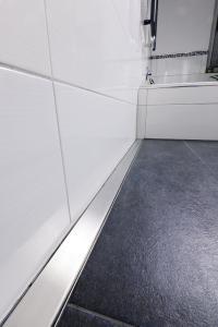 Bündig entlang der Wand verläuft die Rinne vom Typ Elix bis zur eingefassten Badewanne