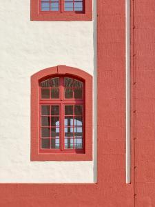 Dunkelrote Anstriche an Eckquadern, Fenster- und Türgewänden gliedern die Architektur. Für diesen Anstrich eignete sich besonders eine wasserabweisende, dabei gleichermaßen dampfdiffusionsoffen Fassaden-Emulsionsfarbe.