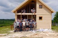 Das Bauteam vor ihrem selbst erbauten Holzhaus