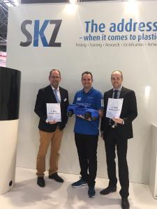 SKZ-Prokurist Dr. Benjamin Baudrit (Mitte) gratuliert Peter Hügen von Sikora (links) und Markus Pest von Coesfeld (rechts) zu ihren Siegen beim Carrera-Rennen mit eigens 3D-gedruckten Fahrzeugen am SKZ-Stand