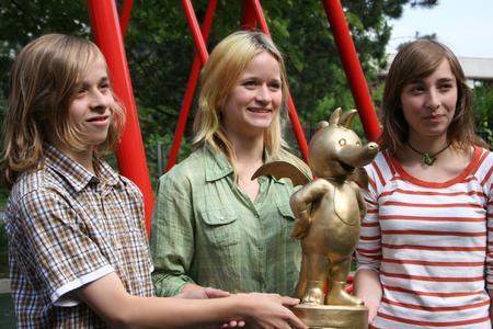 Der 13jährige Marcel und seine Schwester Michelle (15) bedanken sich bei Jackie Weiss (mitte) für Ihr Engagement mit der Überreichung des Goldenen Tabaluga
