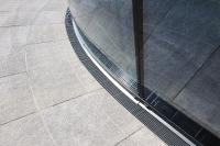 Die Kombination aus den Ausführungen Cubo und Cubo Radial ermöglicht einen Verlauf der Rinnen, der sich dem der Fassade optimal anpasst. So greifen die Produkte der Firma Richard Brink die Formgebung der Messehalle auf und schließen diese zum Außenbereich hin ab.