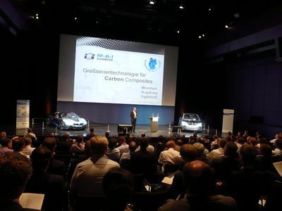 Über 300 Gäste waren in die BMW Welt in München gekommen, um Einblicke in die CFK-Verwendung in der Automobilindustrie zu erhalten. Das Spitzencluster MAI Carbon – im Bild Referent Prof. Klaus Drechsler, Inhaber des Lehrstuhls Carbon Composites an der TU München, hat sich auf die Fahnen geschrieben, den nächsten Schritt zu tun und CFK zur Serienreife zu führen