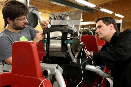 """Prof. Thomas Wagner (rechts) und der Lehrbeauftragte Michael Heyse (links) montieren ein Laptop an einem Sitzplatz der Achterbahn """"Blue Fire"""""""