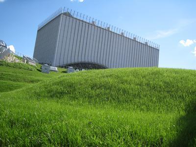 Rasenflächen in geschwungener Form präsentieren das Hauptgebäude, das mit der Zeit ringsum Grün bewachsen sein wird.