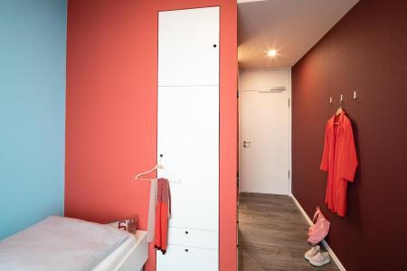 Selbstbewusst und elegant zählt das Anmutungsprofil für das erste Hotelzimmer auf. Von Rot-Tönen dominiert, setzt sich die Bettwand in einem erfrischenden Strandbad-Blau ab / Foto: Caparol Farben Lacke Bautenschutz/Alexandra Lechner