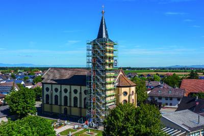 Bild 1 Der Turm der Kirche St. Stephan des Hartheimer Ortsteils Bremgarten ist zur Fassadensanierung und für Putzarbeiten derzeit bis zur Traufhöhe in über 25 m Höhe mit PERI UP Easy in Rahmenbauweise eingerüstet. (Foto: PERI Deutschland)