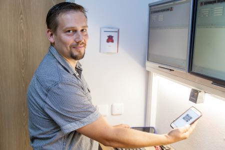 Mirko Mariniak meldet sich mit seinem Barcode an einem BDE-Terminal an