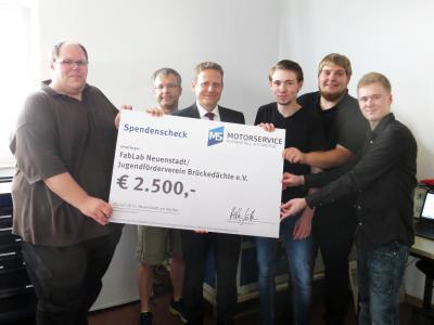 Heiko Göttler (3. v. l.) übergibt Sören Oberndörfer (1. v. l.) und Mitgliedern des FabLabs einen Spendenscheck über 2.500 Euro