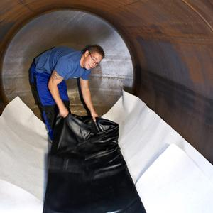 Today, it is very easy to convert a decommissioned steel tank into a rainwater storage tank using the AFRISO AR-SM, an inner lining with magnets. The picture shows the service technician standing on the bottom fleece layer and fitting the lining. The lining will soon be inflated like a balloon using a blower and the magnets will click into position at the tank wall exactly where planned