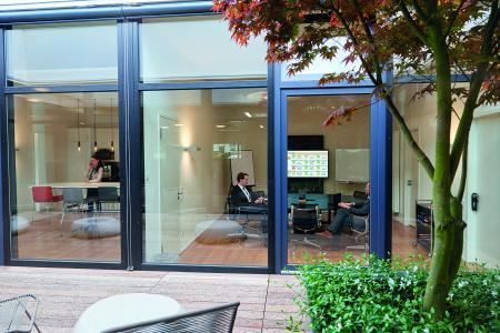 Viel Glas und ein lichtdurchflutetes Atrium schaffen eine offene Arbeitsatmosphäre für die Mitarbeiter