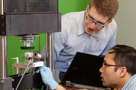 Die Kaiserslauterer Ingenieure Nicholas Ecke (li.) und sein Kollege Dong Hoa Vu untersuchen die Eigenschaften ihrer Kunststoffe an einer Prüfmaschine, dem Stift-Scheibe-Tribometer (Foto: TUK/Thomas Koziel)