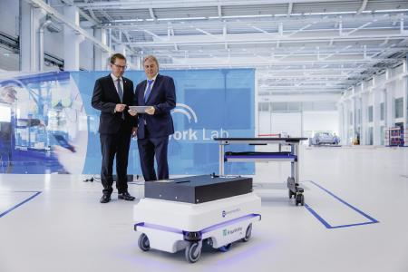 """The mobile workplace of the future: Prof. Dr. rer. nat. Georg Rosenfeld (left), Executive Vice Pres-ident Technology Marketing and Business Models at Fraunhofer, introduces Prof. Dr.-Ing. Peter Gutzmer, CTO at Schaeffler AG, to new technologies that make humans the focus of the factories of tomorrow at the """"Fraunhofer Future Work Lab"""" / Photo: Ludmilla Parsyak, © Fraunhofer IAO"""