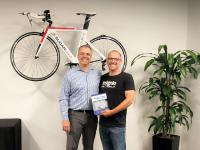 Mirco Müller überreicht stolz eines der ersten Exemplare des neuen Sugar-Handbuchs an den Chief Strategy Officer und Sugar-Mitgründer Clint Oram.