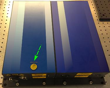 The green arrow points to a chip that can be equipped with up to ten femtosecond lasers. The blue box on which it rests, on the other hand, is a single conventional laser. Picture: CFEL / Neetesh Singh