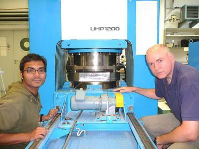 Dr. Shantanu Keshav (links) und Dr. Gundmundur Gudfinnsson vor einer Vielstempel-Presse des Bayerischen Geoinstituts, mit der die Hochdruck- und Hochtemperaturbedingungen im tiefen Erdinneren im Labor simuliert werden