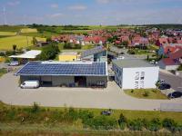 Der Firmenkomplex aus der Luft mit Draufsicht auf die umfangreiche Photovoltaikanlage