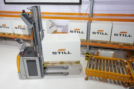 iGo systems: Ein automatisierter STILL Hochhubwagen EXV setzt Vollpaletten aus dem Regal auf die Übergabestationen für den automatisierten STILL Routenzug / Foto: STILL GmbH