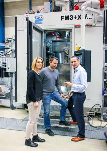 Carina Becker (l.) und Jörg Rodehutskors (Mitte) im Gespräch mit Alexander Wiesner vor einem Fertigungsmodul FM3+Xhd.
