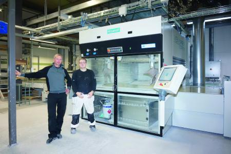 Ven Spray Comfort, Project Manager Andreas Persson and System Operator Tim Hultén in front of the heart of the coating plant—a spray coating machine from Venjakob, Photo: Copyright Venjakob