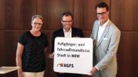 AGFS-Vorstand Christine Fuchs, Dinslakens Bürgermeister Michael Heidinger und NRW-Verkehrsminister Hendrik Wüst präsentieren das neue Schild, mit dem die Stadt Dinslaken ihre Zugehörigkeit zur AGFS demonstriert.