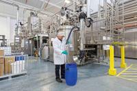 Die Saugarme der Tandem-Absauganlage schaffen die Voraussetzung  für ein staubfreies Eindosieren von pulverförmigen Inhaltsstoffen in  die Mischanlagen.