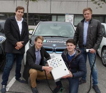 Das Studententeam der Hochschule Darmstadt vor LBF-Forschungsfahrzeugen und der Ladesäule des Fraunhofer LBF, Foto: Fraunhofer LBF
