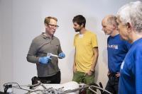 Helfer des Repair Cafés kleben unter Anleitung von Matthias Lükemann (2. v. l.) eine abgelöste Sattelstrebe am Fahrrad