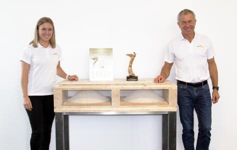 """Carmen und Ferdinand Schneider (Geschäftsleitung) mit dem Architects' Darling Award """"BESTE PRODUKT-INNOVATION ROHBAU"""" für die best wood CLT BOX – DECKE FS."""