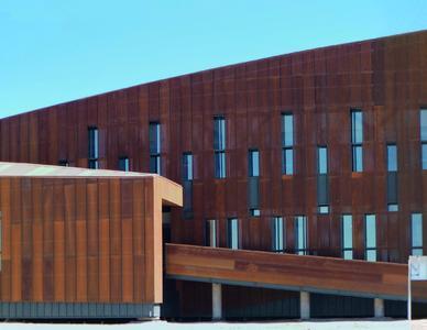 Starke Sandstürme und hohe Temperaturschwankungen gaben den Charakter der Fassade vor: Die Architekten entwarfen eine dichte Gebäudehülle aus Cortenstahl und Glas. Schmale Öffnungen gliedern die Längsseiten der Kuben. Bild: Schüco International KG