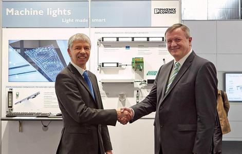 Presentation of the LED machine lights at Hannover Messe 2013: Wolfgang Keller (left), Head of the Optoelectronic Systems business unit, and Martin Müller, Head of the I/O and Networks business unit at Phoenix Contact Electronics, showcase the result of their collaboration