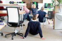 Was machen die denn da im Büro? Zum gesünderes Verhalten am Arbeitsplatz gehört auch die eine oder andere Fitnessübung.