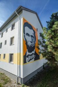 """Ein Großporträt von Abraham Lincoln, dem 16. US-Präsidenten, ist Blickfang auf der Giebelseite eines Bestandhauses, in dem jetzt Studenten wohnen. Es stellt den Bezug zum Namen des einstigen Wohngebietes der amerikanischen Soldatenfamilien, """"Lincoln-Siedlung"""", her (Foto: Caparol Farben Lacke Bautenschutz/blitzwerk.de)"""