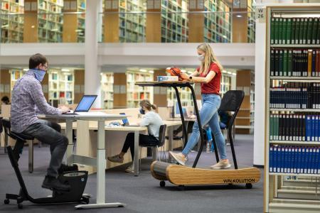 Studentin Luisa Frech und Georg Peter vom Studentischen Gesundheitsmanagement testen in der Universitätsbibliothek der TU Ilmenau die dynamischen Arbeitsplätze (© TU Ilmenau/Michael Reichel
