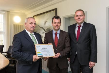 Umweltminister Dr. Till Backhaus überreicht WEMAG-Vorstandsmitglied Caspar Baumgart und WEMAG-Vertriebsleiter Michael Hillmann (v. l.) die Urkunde für den Erwerb von 500 MoorFutures-Zertifikaten (Bild: WEMAG/Stephan Rudolph-Kramer)