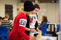 Verschiedene Experimentierstationen laden Schüler ein, selbst aktiv zu werden. Hier wird gerade ausprobiert, wie stabil eine Brücke aus Papier sein kann. Foto: IJF/Tamara Hegedüs