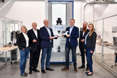 The founding generation (Therese Havemann, Klaus Havemann, Dr. Axel Hunsche) of German testing machine manufacturer TesT passing the baton to the succeeding generation (Jan Havemann, Arne Havemann, Julia Kiewitter (neé Hunsche)) in the form of a spanner
