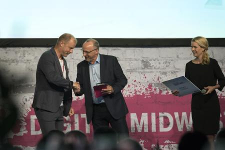 IoT-Venture-Geschäftsführer Jürgen Veith (links) nimmt die Auszeichnung von Alfred Volk, Leiter Geschäftskundenvertrieb bei der Deutschen Telekom, entgegen