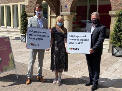 """Sie präsentierten das neue """"Ortsschild"""": NRW-Verkehrsminister Hendrik Wüst, Bürgermeisterin Mechtild Schulze Hessing und AGFS-Pressesprecher Michael Blaess."""